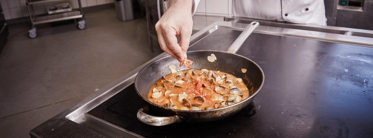 Tomatensauce und Peperoncini hinzufügen. Sauce ein wenig reduzieren.