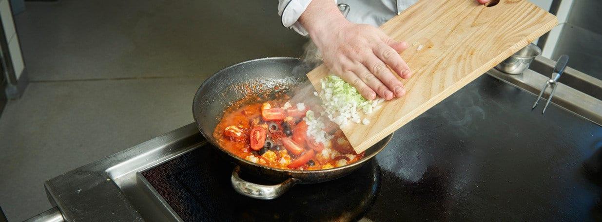 Frühlingszwiebeln, Oliven, Tomaten sowie Petersilie zugeben und kurz köcheln lassen.