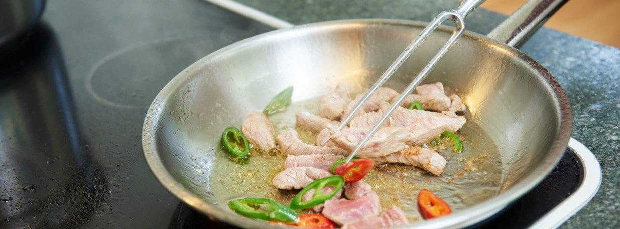 Zwiebeln, Knoblauch, Peperoncini und Kalbsfleischstreifen scharf anbraten.