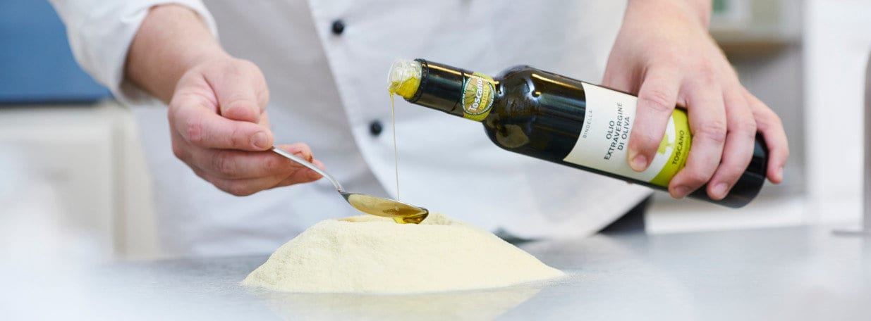 Aufgelöste Hefe, Wasser, Olivenöl und Salz zum Pizzamehl geben. Ca. 20 Minuten kneten.