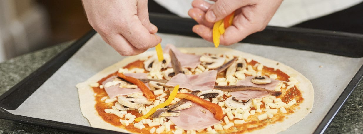 Teig dünn ausrollen. Tomatensauce in kreisrunden Bewegungen auf den Teig geben und mit restlichen Zutaten belegen.