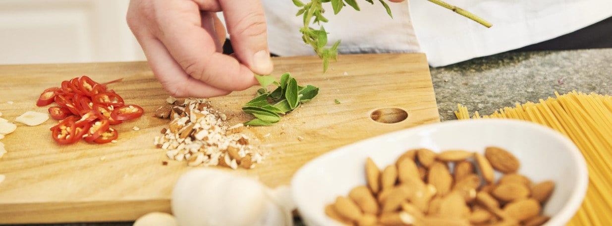 Mandeln grob hacken. Peperoni in Würfelchen schneiden und Oreganoblätter abzupfen.