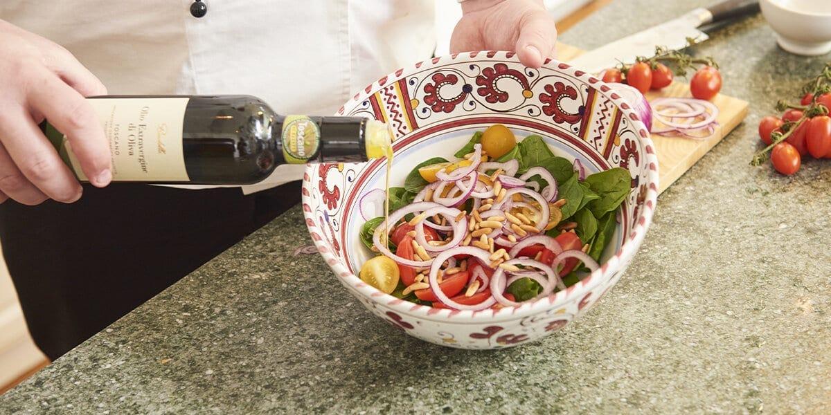 Datteltomaten, Zwiebelringe, Spinat und Pinienkerne in einer Schüssel mit Olivenöl vermischen.
